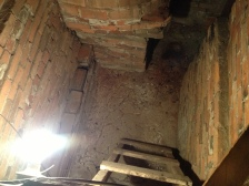 Looking down into the hidden space. At the top left is the shell of a brick oven. At the top right you can see where another passage way, which was accessed from the living room. The owner of this home said that it was used to hide during raids by the natives.